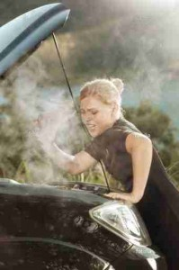 woman leaning in under the hood of a over-heated car